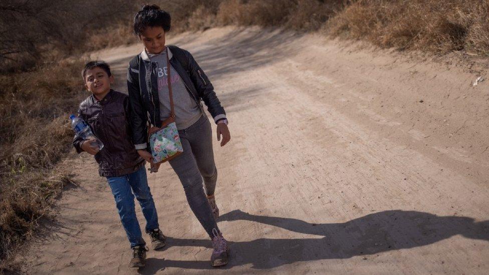 Dos niños hondureños caminan en una carretera de tierra en Peñitas, Texas, después de cruzar la frontera a través del Río Bravo.