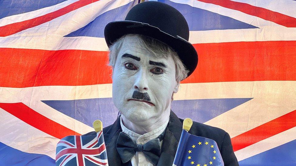 Hombre maquillado como Charlie Chaplin con banderas de Reino Unido y la Unión Europea