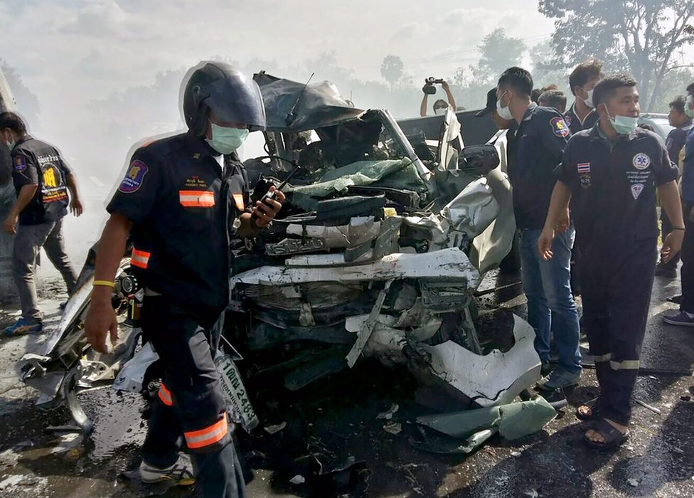 Thai rescue workers inspect a wreckage pickup truck after collided with a passenger van vehicles and both were burned in the accident at a highway in Chonburi province, Thailand, 2 January 2017