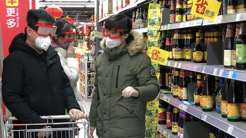 超市裏戴口罩購物的消費者