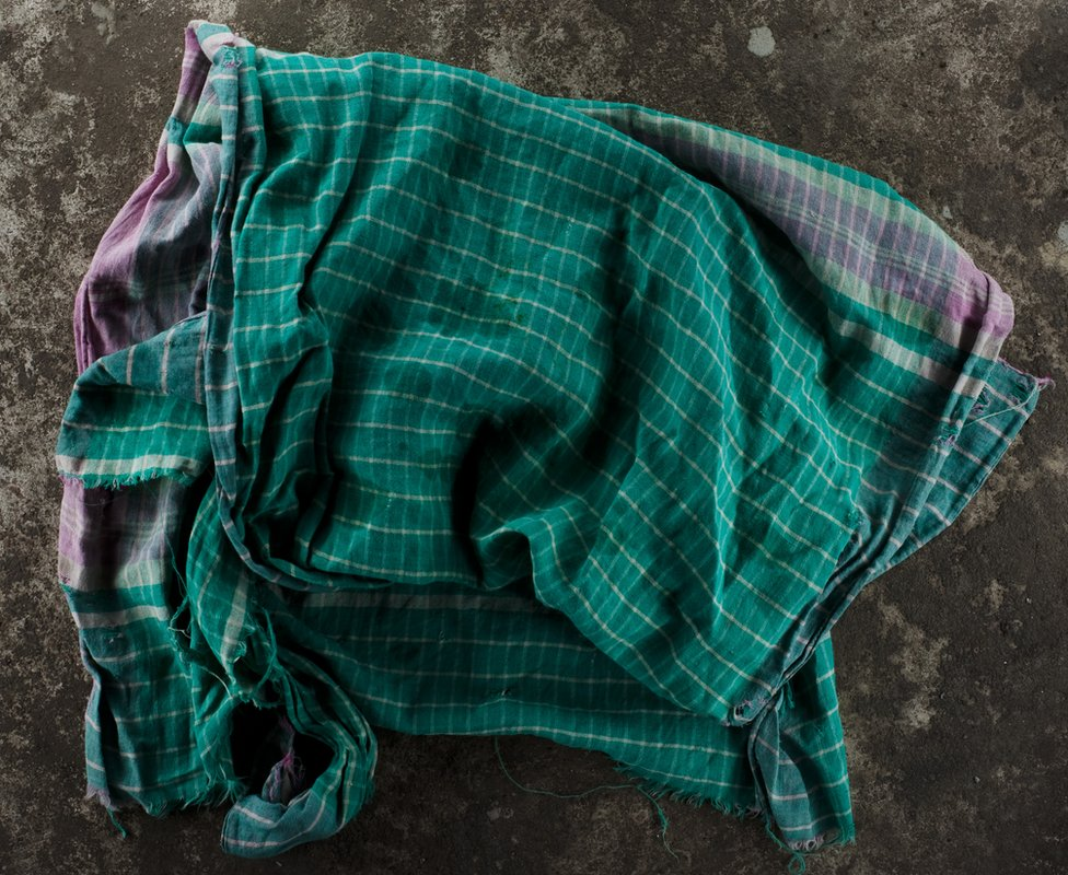 A piece of fabric lying on concrete. Gamcha. Part of 'Crossfire', a photo story by Shahidul Alam. February 13, 2010.