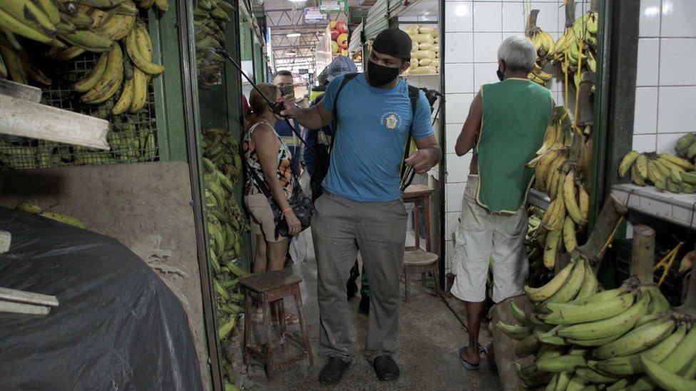 Homem faz dedetização em mercado em Manaus