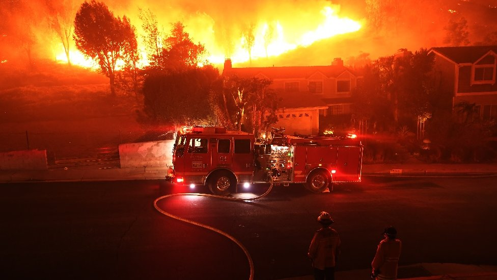 Los Angeles County firefighter looks on as the out of control Woolsey Fire explodes behind a house in the West Hills neighborhood