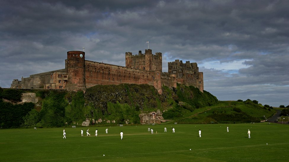 Cricketers play on pitch next to Bamburgh