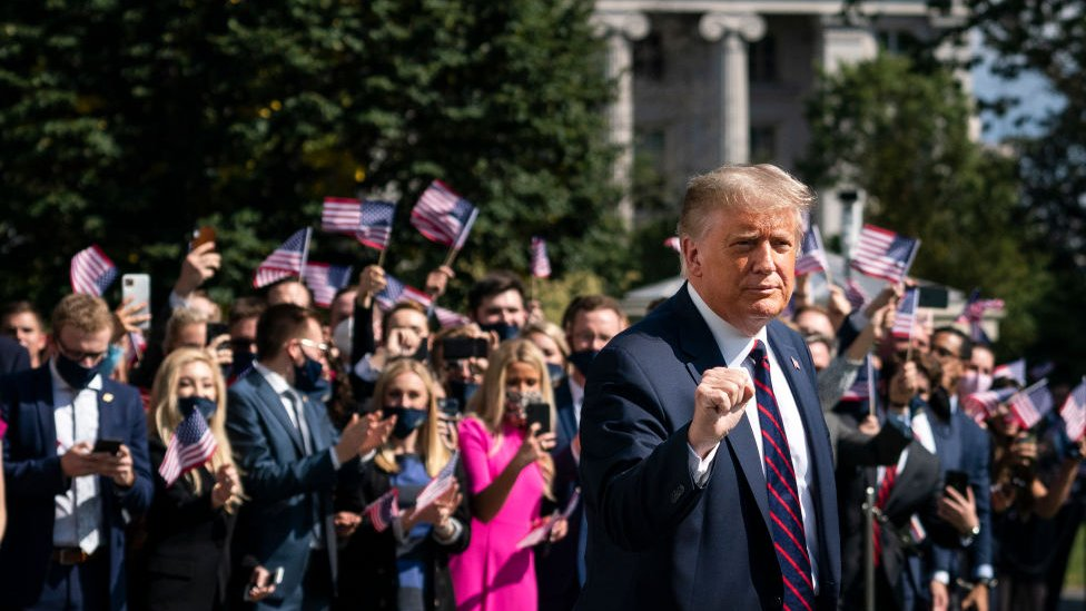 President Donald Trump gestures as White House interns cheer him on as he leaves the White House on September 29, 2020