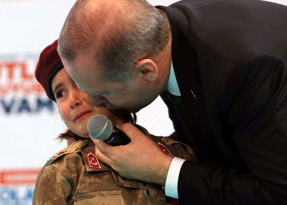 Turkish President Recep Tayyip Erdogan kisses a girl dressed as a Turkish soldier during the 6th ordinary provincial congress of the Justice and Development Party (AKP)