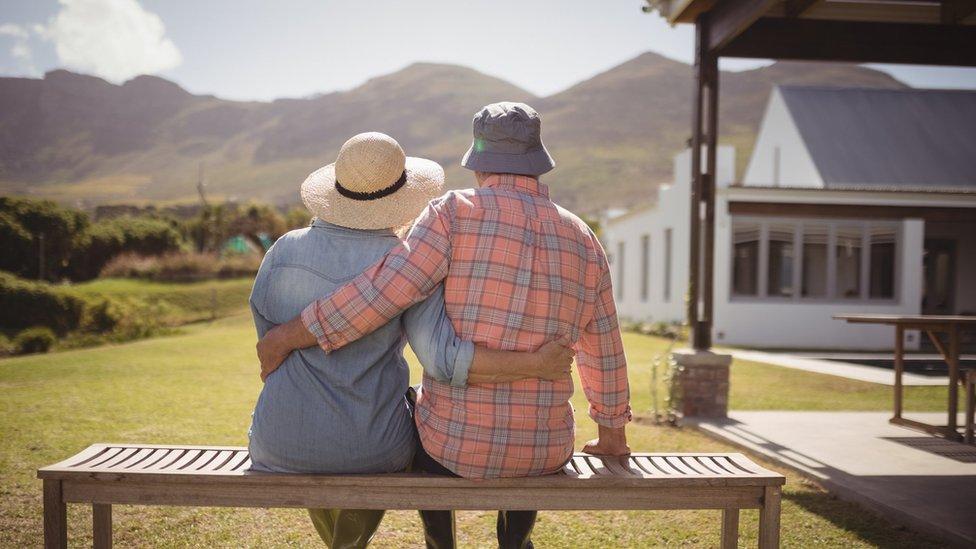Stariji par sedi na klupi