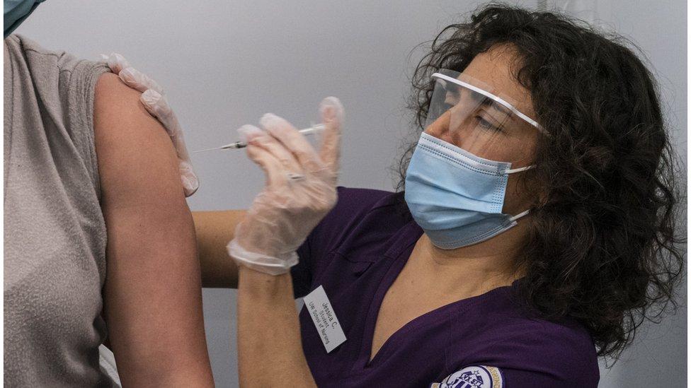 عاملة طبية أمريكية تحقن امرأة باللقاح