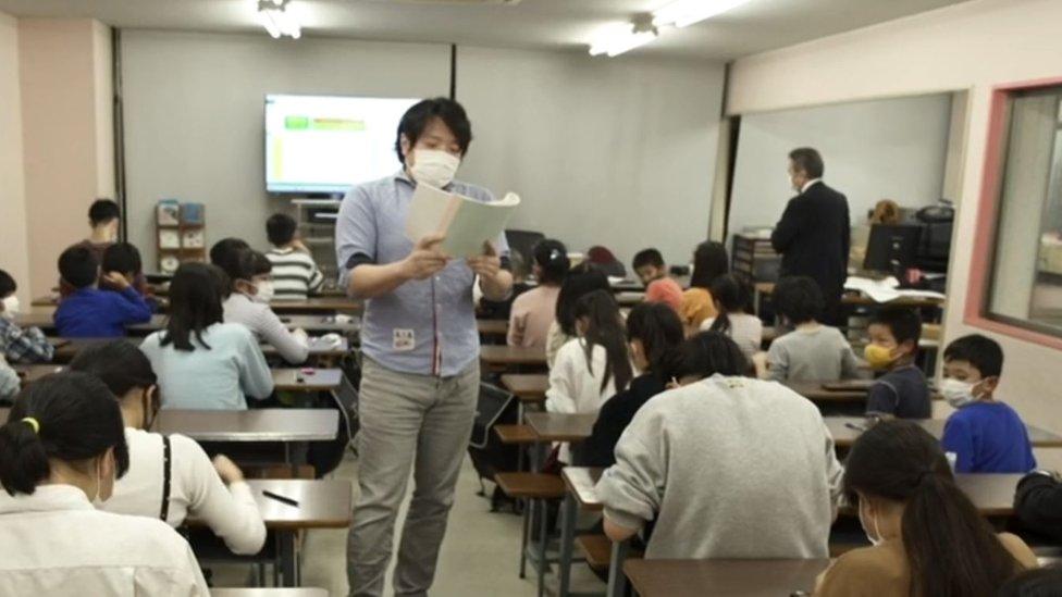 Profesor dictando números en la clase de ábaco.