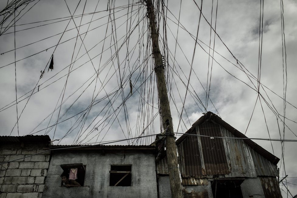 A man stick out his head outside his small window along with the tanggled electrical lines in Area A, Gate 5, Parola Tondo.
