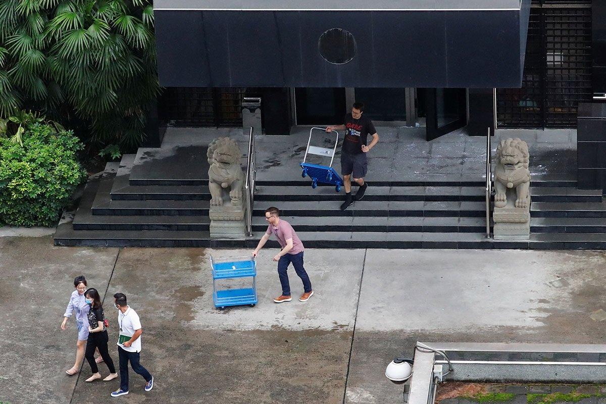 美國駐成都總領館內的徽標已經被取下,工作人員正忙著搬運物品。