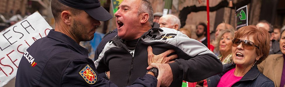 A protester is held back by a policeman at Madrid's High Court where Rodrigo Rato, former chairman of rescued bank Bankia and former head of the International Monetary Fund answered allegations of misusing company credit cards on 16 October 2014 in Madrid, Spain