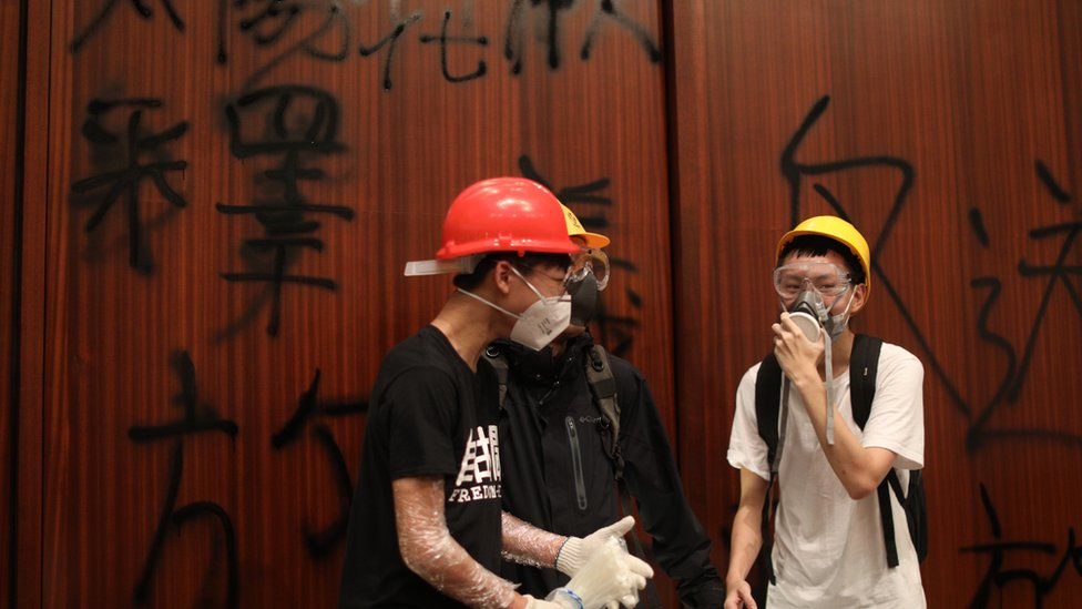 Protesters stand by a wall covered in graffiti
