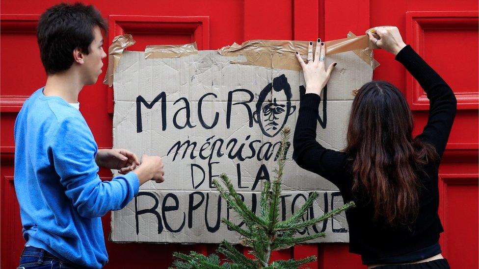 """متظاهران يعلقان لافتة على باب مدرسة مكتوب عليها """"ماكرون لا يحترم الجمهورية"""""""