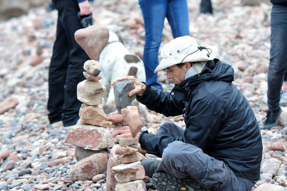Man creating stone stack on a beach