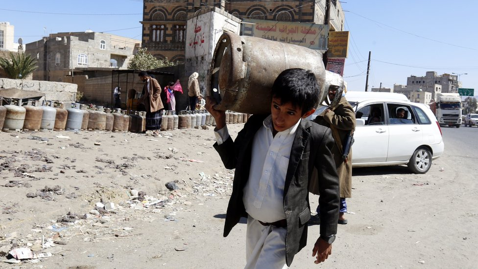 A Yemeni boy carries an empty gas cylinder as others wait for gas supplies in Sanaa, Yemen (7 November 2017)