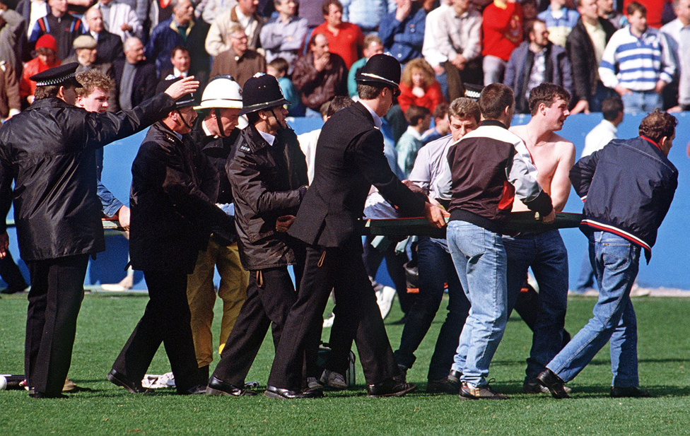 Police and fans carry away injured from the scene at Hillsborough