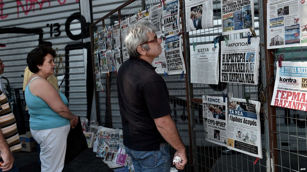 People read newspaper headlines in Athens, 13 July 2015