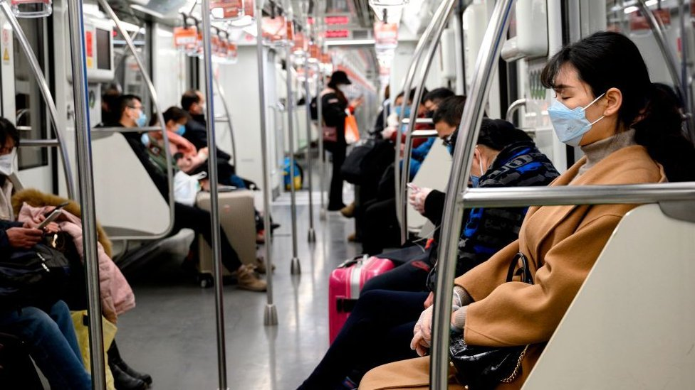 Personas usan máscaras en el tren de Shanghái.
