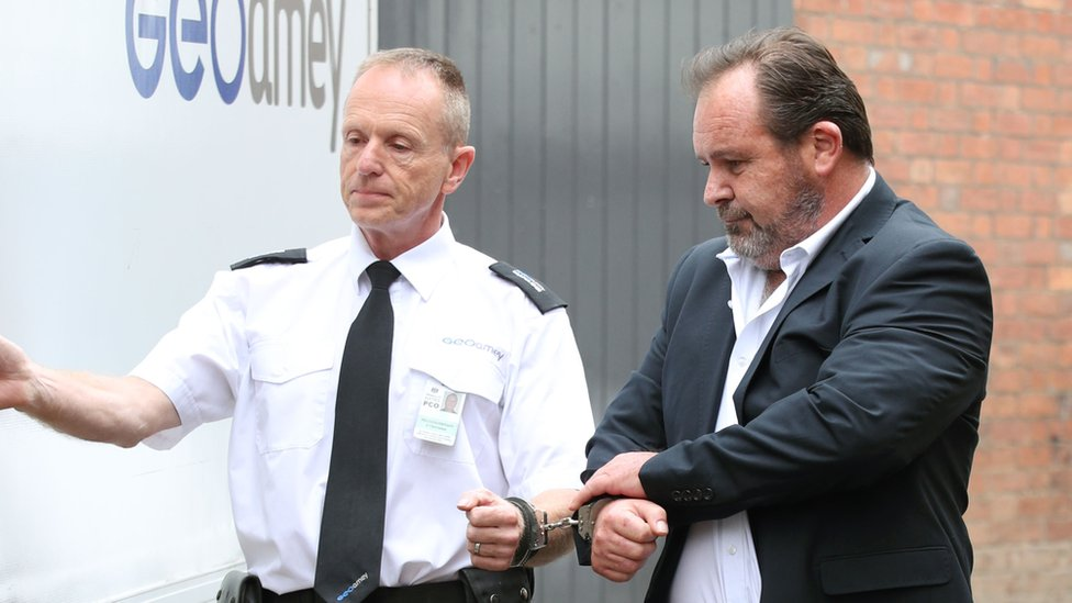 Monaghan being led to a prison van