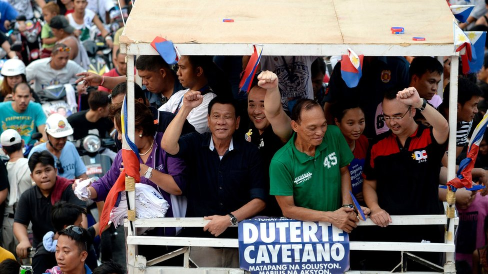 Rodrigo Duterte (centre, in black) gestures to the crowd from the top of a packed campaign bus