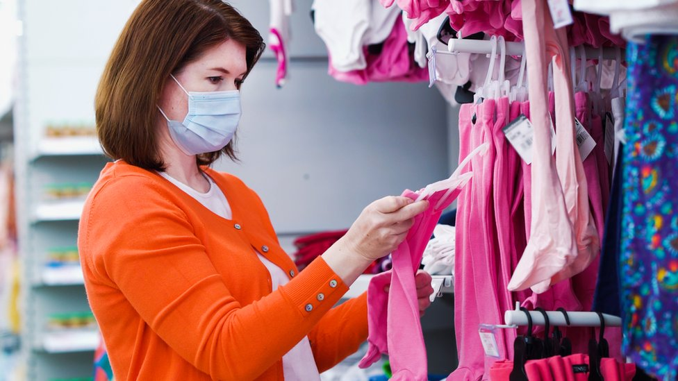 A woman looking at children's clothing