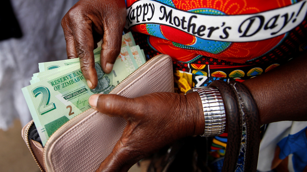 "A woman poses with Zimbabwe""s new two dollar banknotes as customers queue outside a bank in Harare, Zimbabwe,"