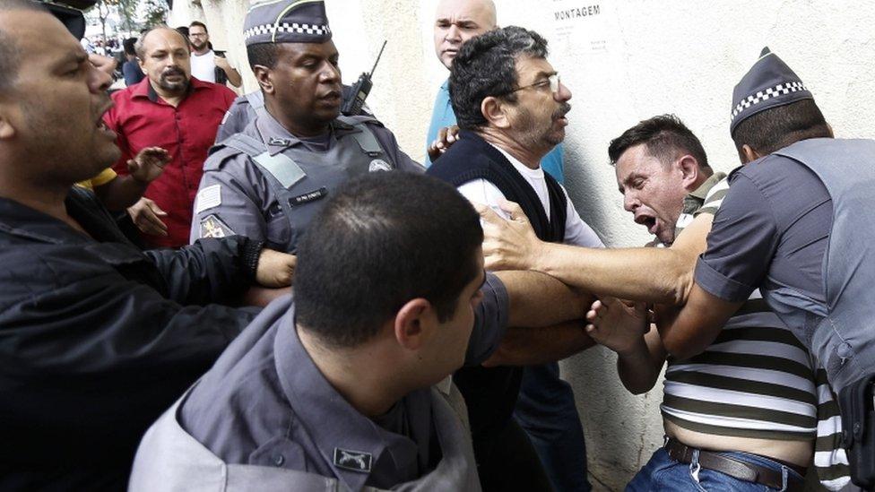 A supporter of former Brazilian president Luiz Inacio Lula da Silva struggles with police near his home, 4 March