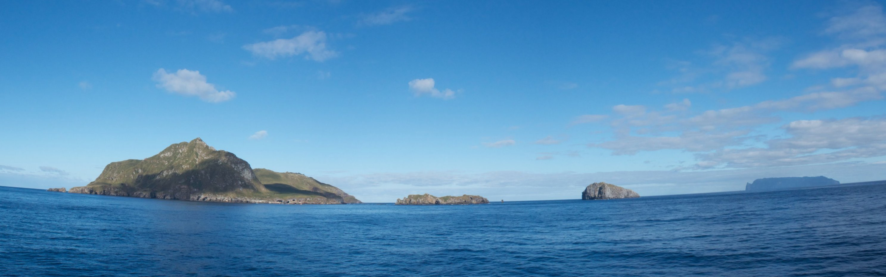 Panoramic views of Nightingale Islands, with the dark outline of Inaccessible Island in the distance