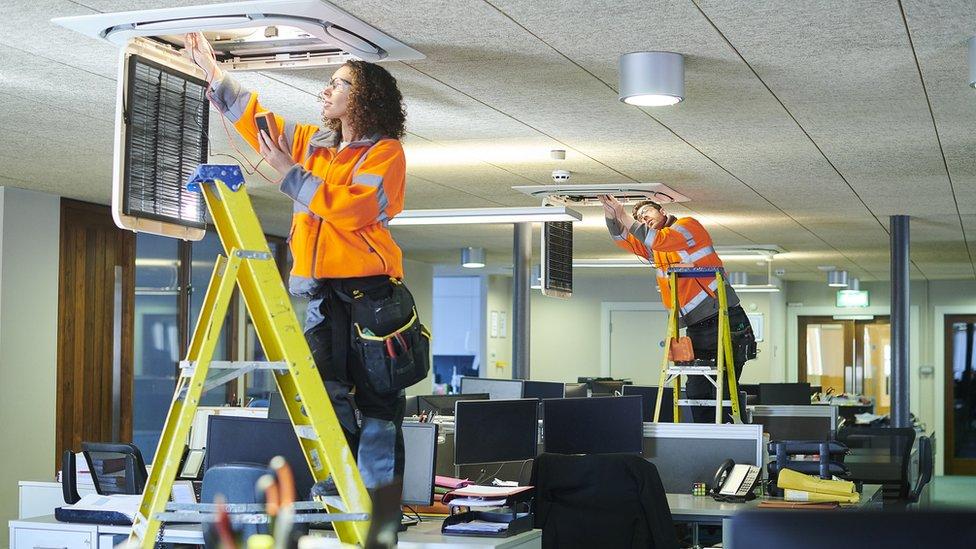 Trabajadores instalando aires acondicionados.