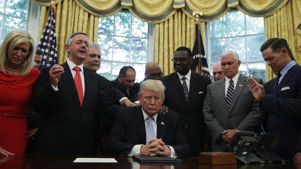 El presidente Donald Trump, el vicepresidente Mike Pence y líderes religiosos rezan en la Oficina Oval.
