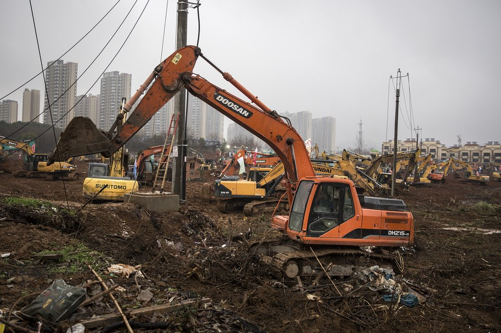 A digger is seen on the construction site of Huoshenshan hospital