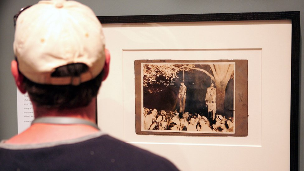 Un hombre observa una exposición de fotografías sobre los linchamientos en Estados Unidos.