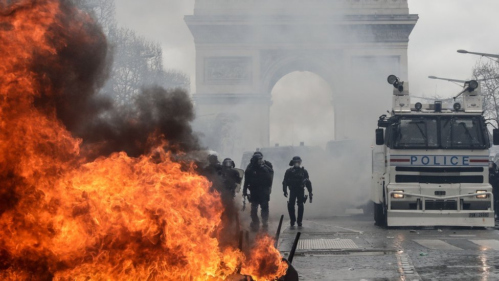 "French riot police forces stand behind a burning barricade on the Champs-Elysees in Paris on March 16, 2019, during the 18th consecutive Saturday of demonstrations called by the ""Yellow Vest"" (gilets jaunes) movement."