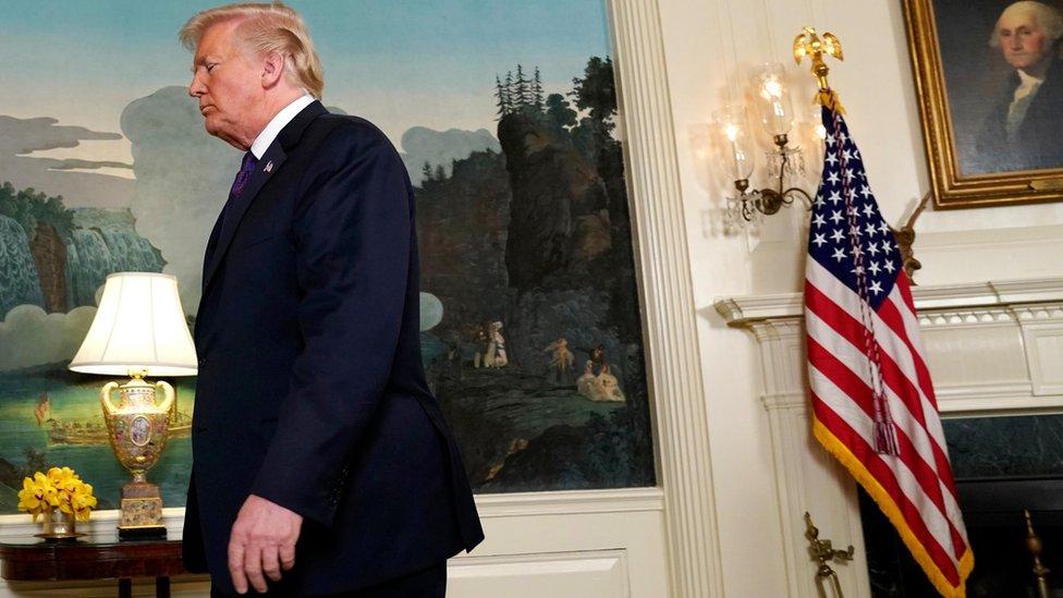 Donald Tramp izlazi sa konferencije za štampu, američka zastava u pozadini