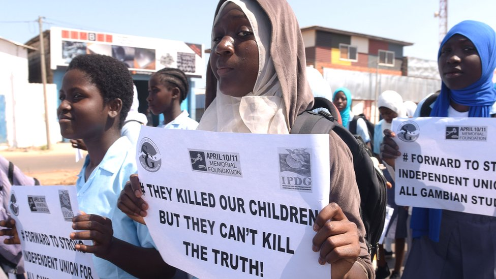 """Demonstrators hold placards reading """"They killed our children but they can't kill the truth"""" during a march in rememberance of victims of The Gambia's former regime, in Serekunda - April 2017"""