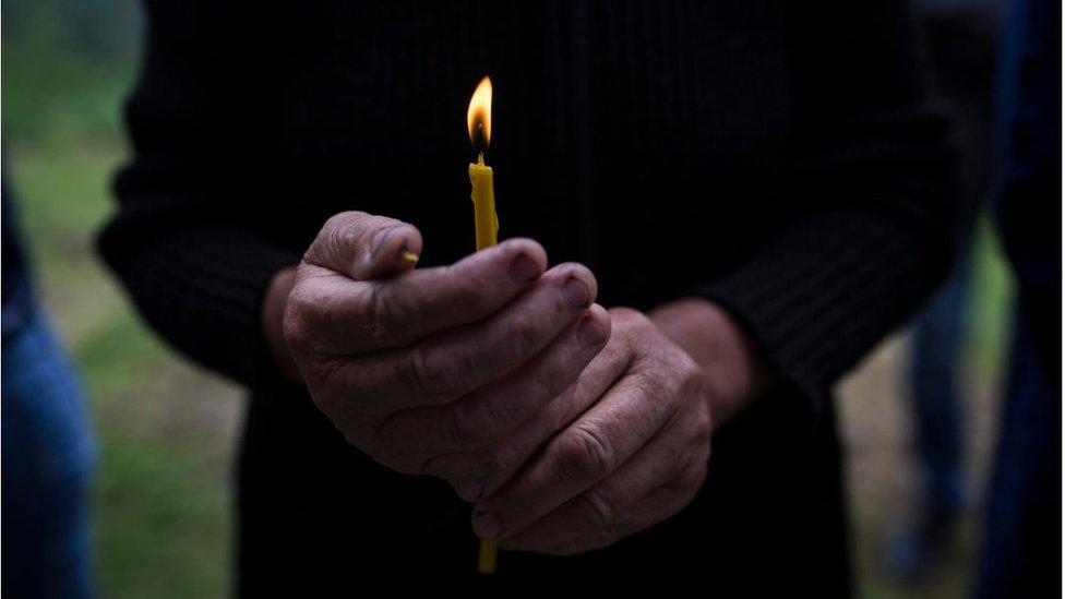 Žena drži sveću u rukama