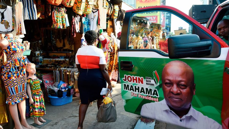 A woman walk past a campaign poster, pasted on car door, of former president and National Democratic Congress (NDC) candidate John Dramani Mahama in Accra on December 3, 202