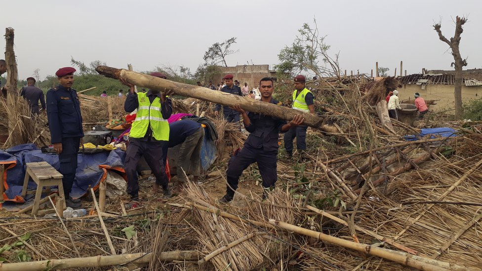 Nepalese police search damaged homes after a storm struck Managadwa village in Bara district, Nepal, 1 April 2019