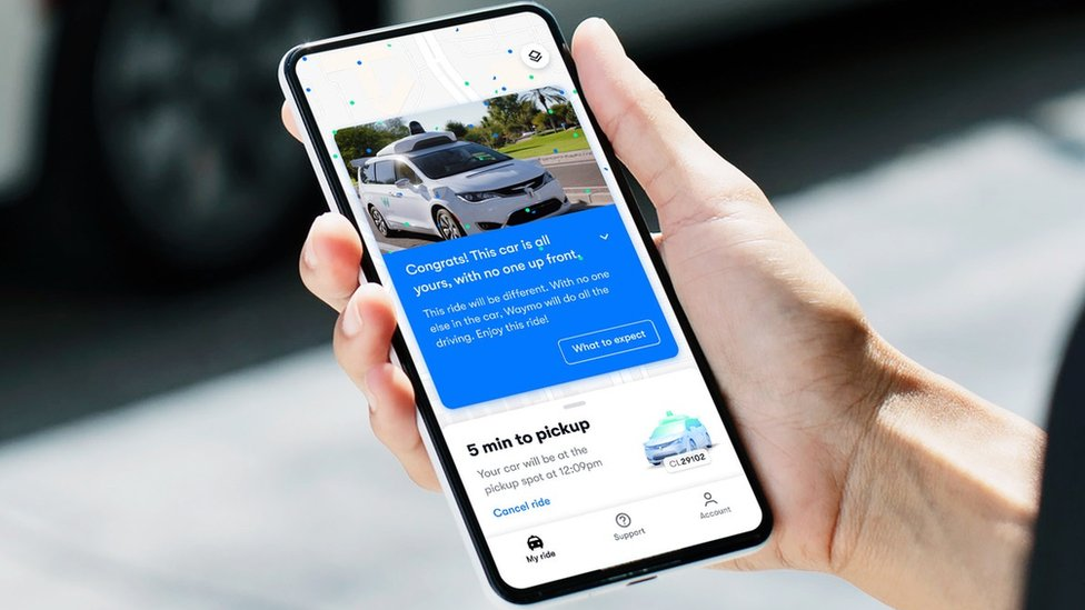 Person holding phone with Waymo app on
