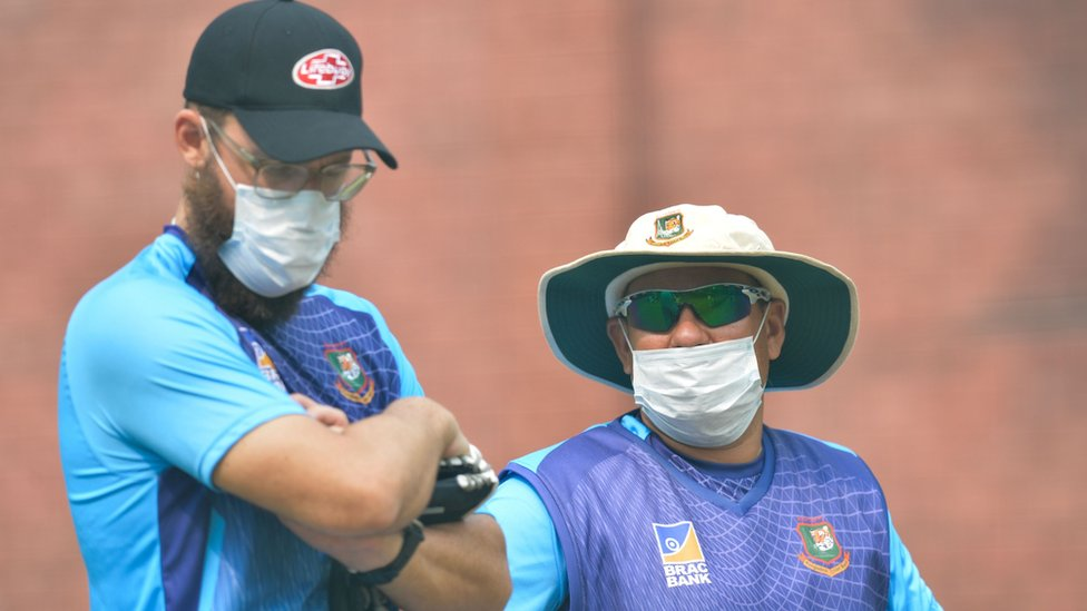 Bangladesh cricket team head coach Russell Domingo (R) and bowling coach Daniel Vettori wearing face masks watch the team during a practice session at Arun Jaitley Cricket Stadium in Delhi on November 1, 2019,