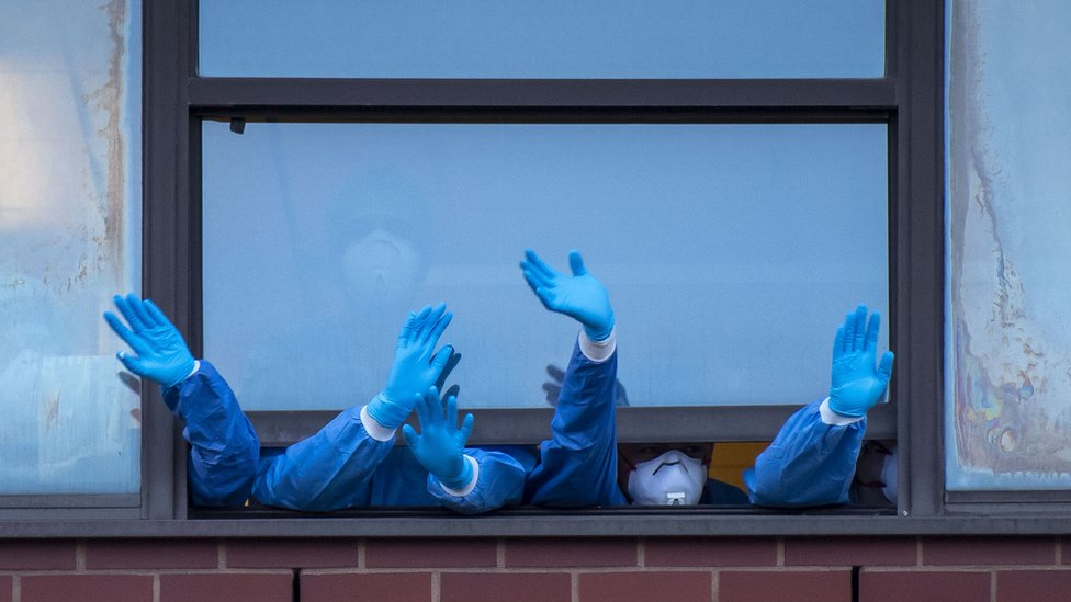 NHS staff wave out a window