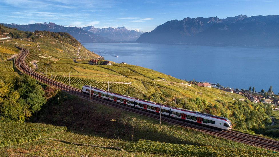 A Swiss train passes a lake through the countryside, with mountains in the background.