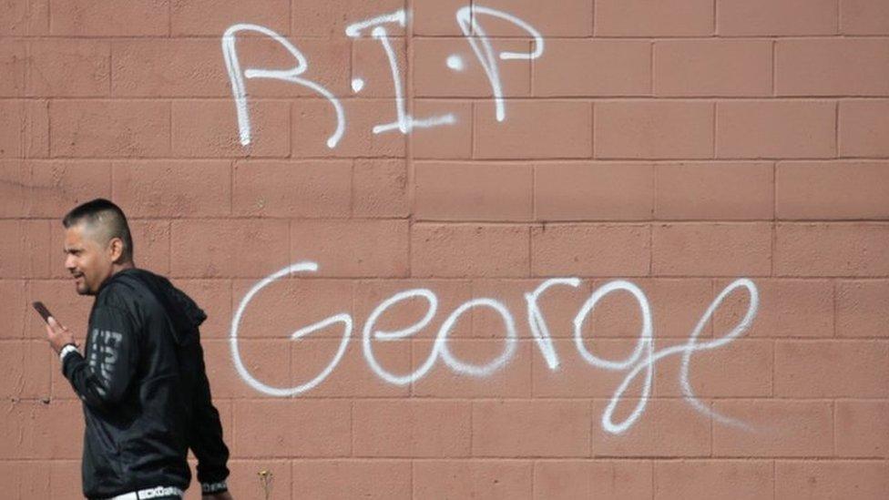 Un ciudadano camina frente a un mensaje de despedida a George Floyd