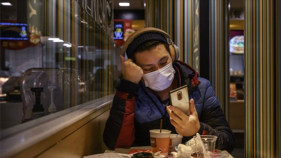 A man wears a protective mask while eating in a McDonald