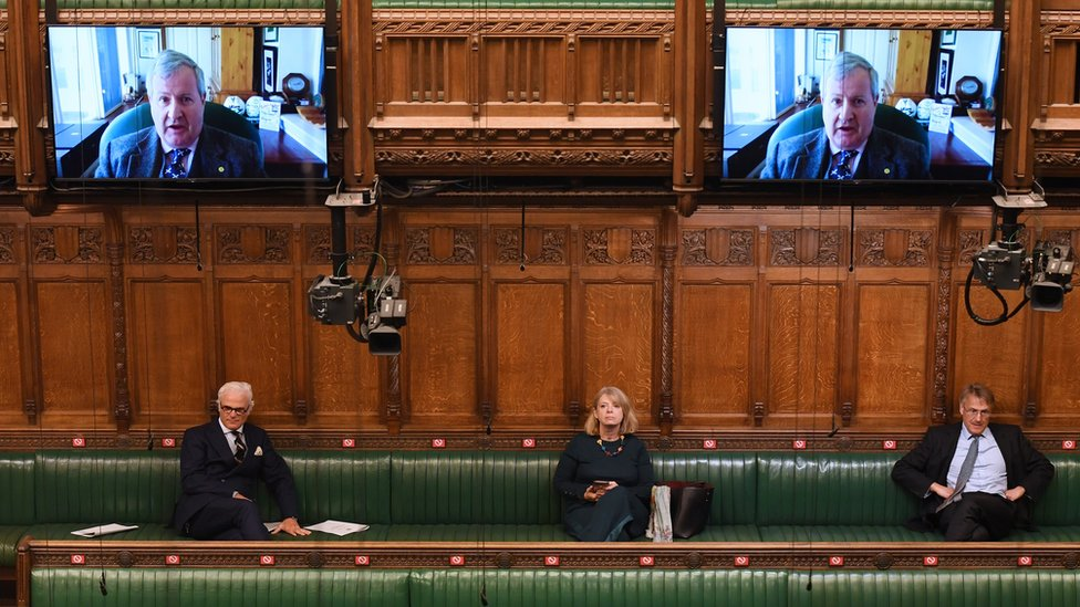 MPs sit in the chamber listening to a colleague on Zoom