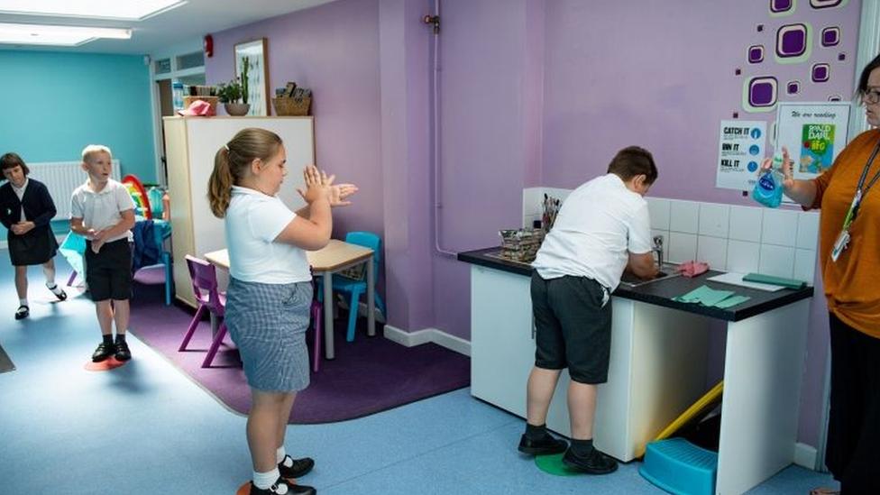 Crianças lavando a mão em escolas britânicas