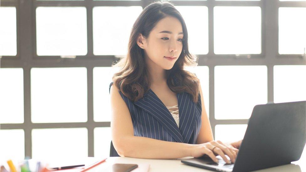 Una joven china, con su computador.
