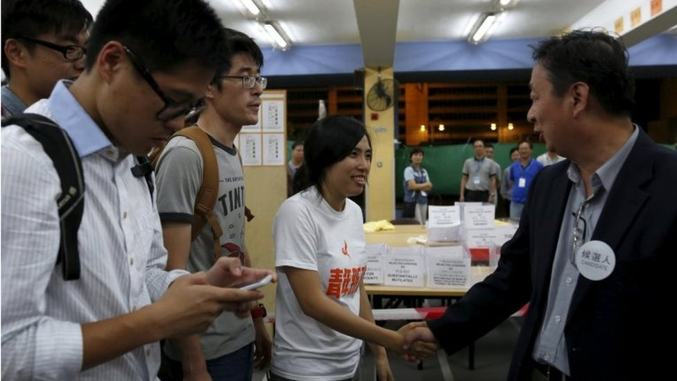 Ms Kwong shakes hands with her opponent in the election