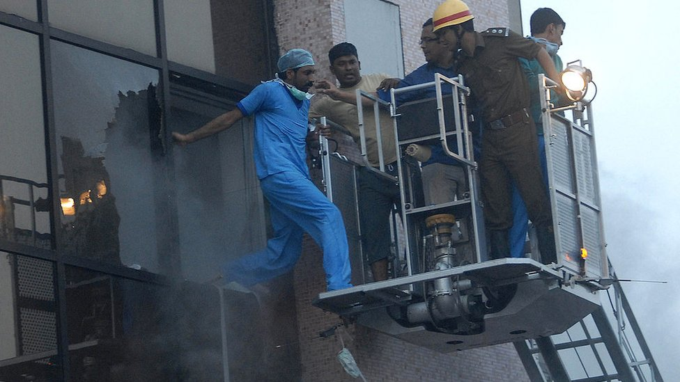 Rescue workers evacuate a hospital staff member as a fire engulfs the Advance Medicare and Research Institute (AMRI) hospital in the eastern Indian city of Kolkata on December 9, 2011